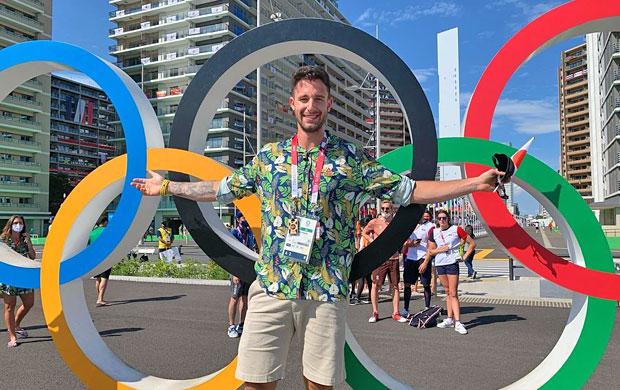 Lucas Verthein em frente aos arcos olímpicos na Vila Olímpica em Tóquio
