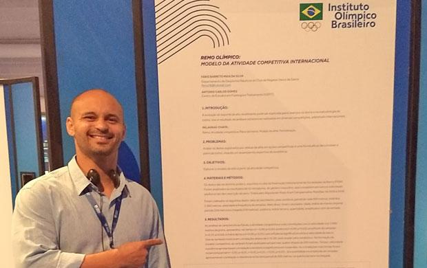 Fábio Barreto ao lado de seu pôster durante o Congresso Olímpico Brasileiro