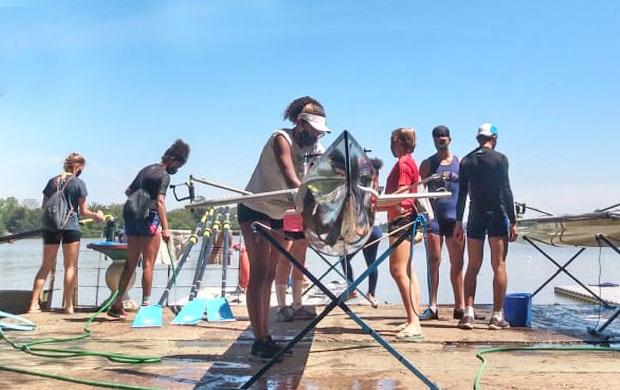 Atletas limpam e preparam barcos para as atividades na Ilha do Pavão, em Porto Alegre